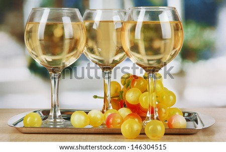 White wine in glass on salver on window background - stock photo