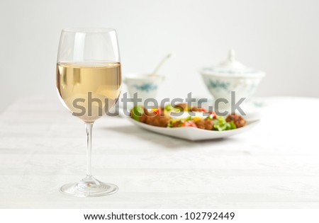 White wine in glass, salad behind