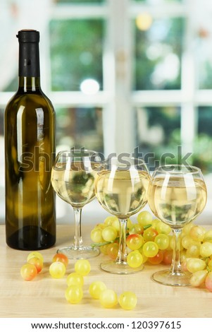 White wine in glass with bottle on window background - stock photo