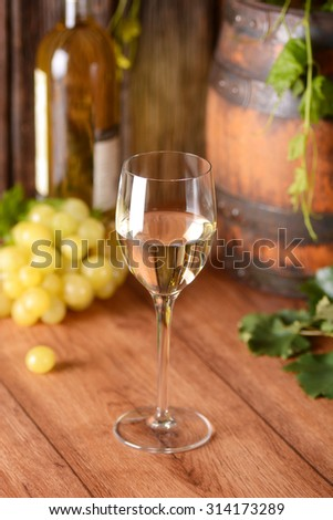 white wine in the glass chalice on the wooden table