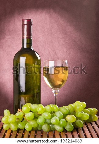 White wine in wine glass and green grapes