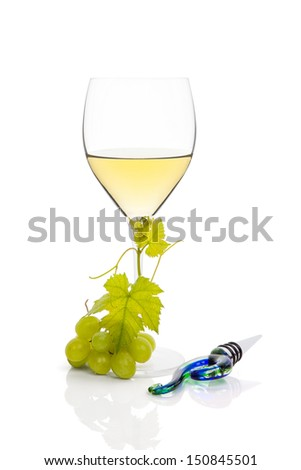 White wine in wine glass with green grapes and wine stopper isolated on white background. Luxurious wine still life. - stock photo