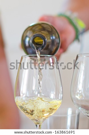 White wine is pouring into wine glass - stock photo