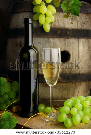 White wine on background of old wine barrel with grapes - stock photo