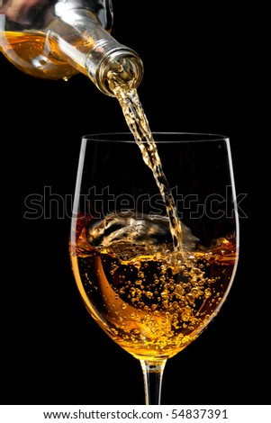 White wine poured in a glass isolated on a black  background
