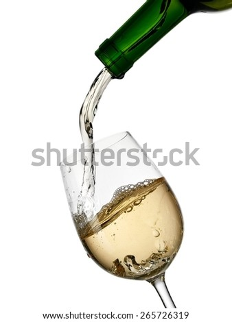 White wine pouring from a green bottle - stock photo