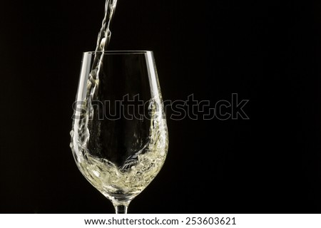 White wine pouring in a glass - stock photo