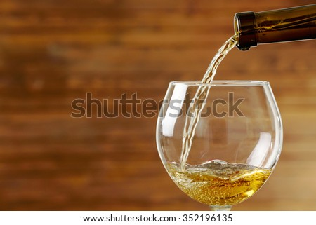 White wine pouring in glass on wooden background - stock photo