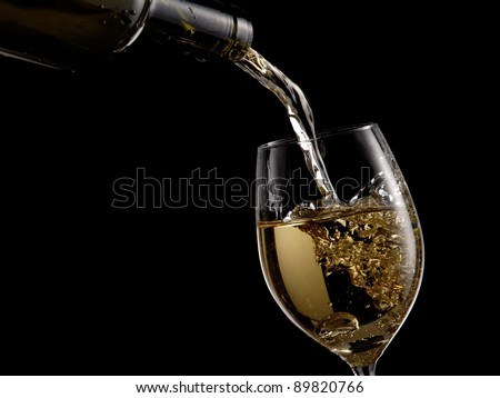 White wine pouring into a glass on black background - stock photo
