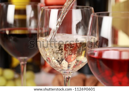 White wine pouring into a wine glass. Selective focus on the white wine. - stock photo