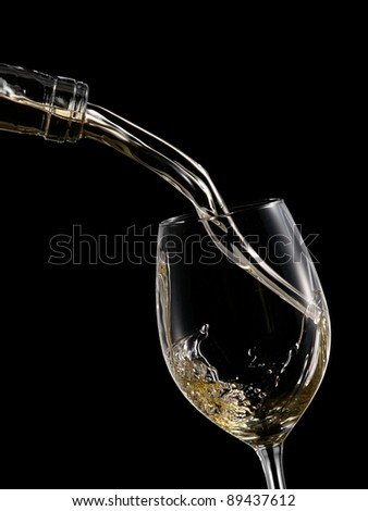 White wine pouring into a wineglass on black background