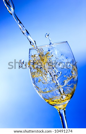 White wine pouring into glass over blue background - stock photo