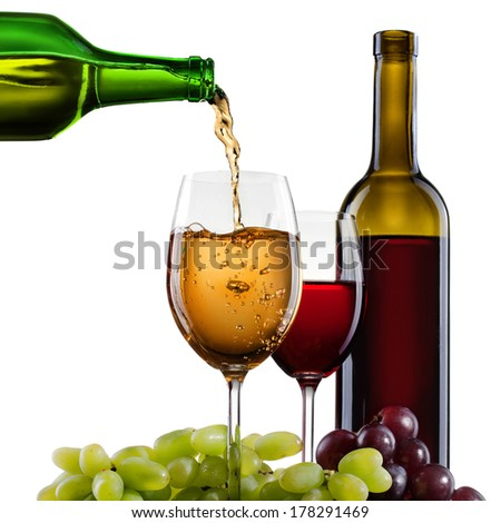 White wine pouring into glass with grape and bottles isolated - stock photo
