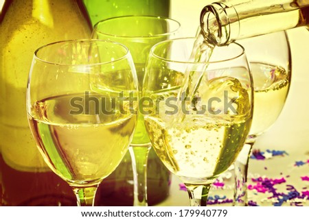 White Wine Pouring into Glasses - white wine being poured into glasses at a party, with an instagram effect. - stock photo