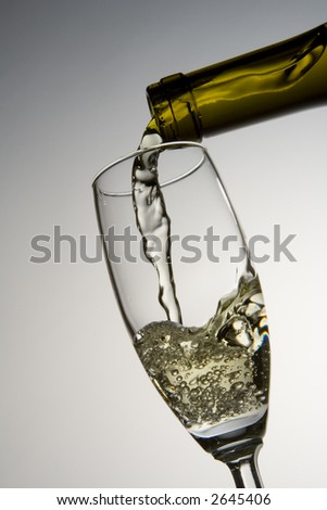 White wine pours into wineglass from bottle