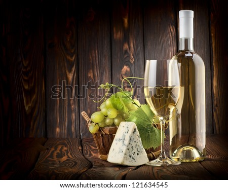 White wine with grapes and blue cheese on a wooden background - stock photo