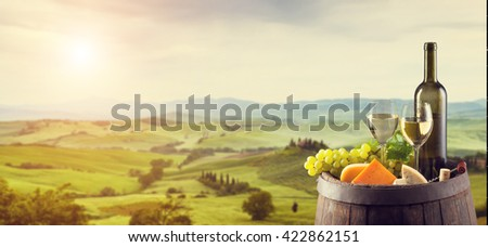 White wine with wooden barrel on vineyard in Tuscany, Italy - stock photo