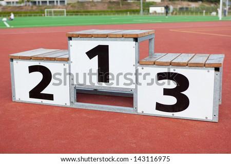 white winners podium standing on soccer field - stock photo