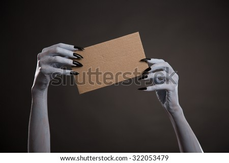 White witch hands with black nails holding blank cardboard, Halloween theme  - stock photo
