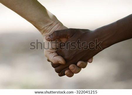 White Woman and African Girl Holding Hands Friendship Symbol. African Peace Symbol. White woman holds hands with a native African girl, in Bamako, Mali. A black child and a white woman hold hands.  - stock photo