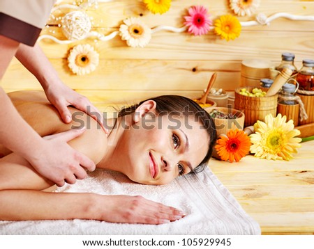 White woman getting  massage in wooden spa. - stock photo