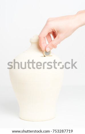 White woman hand inserting coin in a moneybox