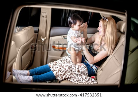 White woman with a child of one year in the light leather car interior change clothes  - stock photo