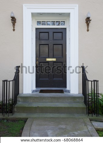 White wood bordered black door of beige stucco house - stock photo