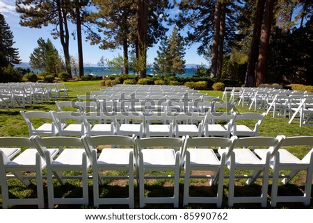 White wood event chairs, set up in neat rows, in a beautiful outdoor garden setting. The scene includes a view of trees, bushes and a picturesque lake in the background. - stock photo
