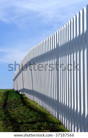 White wood garden picket fence on green grass over blue sky