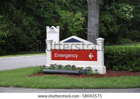 White wood sign with the words emergency on.