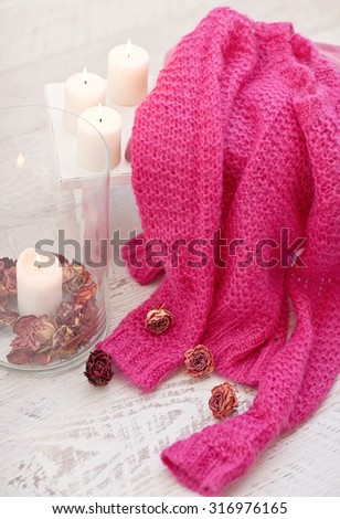 White wood stool with candles, dry roses and pink wool sweater, pullover. Autumn mood. - stock photo