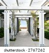 White Wooden Arbor/Pergola with blue sky in distance. - stock photo