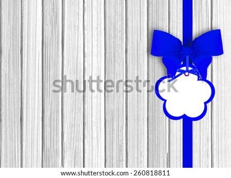 white wooden background with beautiful blue bow with tag - stock photo