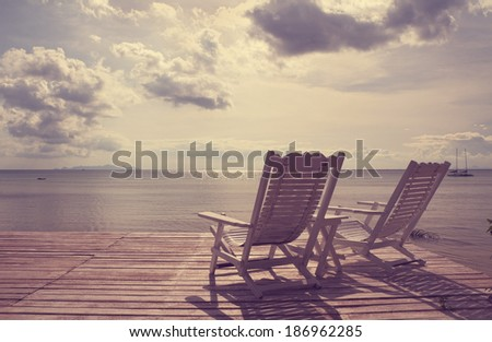 White wooden beach chair facing seascape,vintage filter effect - stock photo