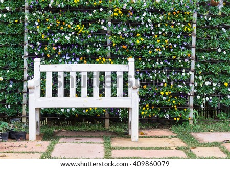 White wooden bench in front of the vertical garden. - stock photo