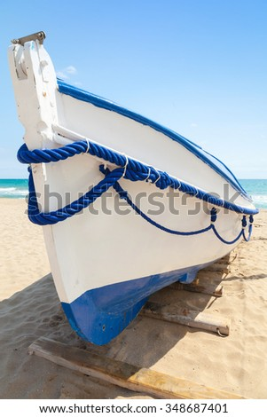 White wooden boat lays on sandy beach, Mediterranean sea coast of Spain - stock photo