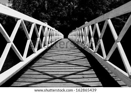 White wooden bridge leading to mystery forest on the opposite shore in moonlight, image in black and white. - stock photo