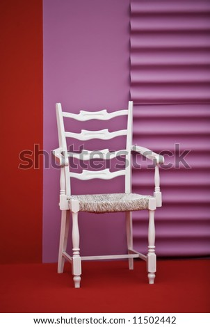 White wooden chair in a very colorful red and pink room. - stock photo