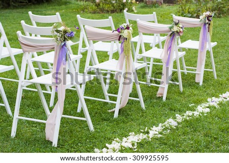 White Wooden Chairs Decorated With Bows Flowers And Path Of Petals On Wedding Ceremony Outdoors