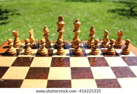 White wooden chess pieces on a chessboard, green grass as background  - stock photo