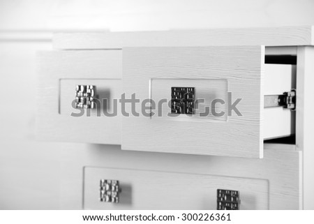 White wooden chest of drawer, close up. Open drawer