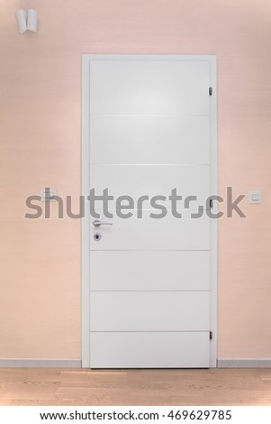 White wooden closed door inside modern interior