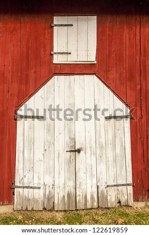 White wooden doors on old red barn - stock photo