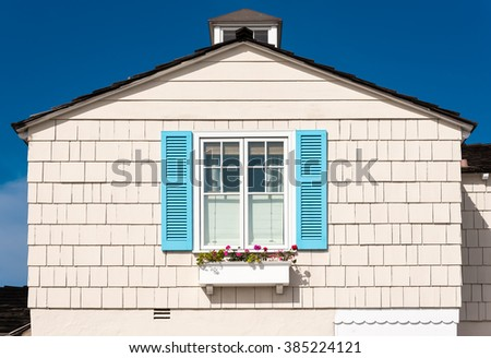 white wooden facade with blue shutters and flowers