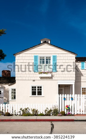 white wooden facade with blue shutters and flowers - stock photo
