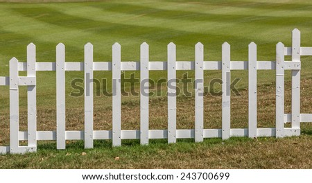 White wooden fence with green meadow background.