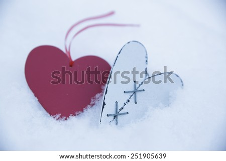 White wooden heart in the snow with red heart on blurring background - stock photo
