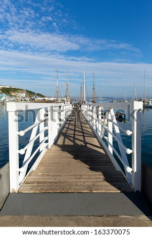 White wooden jetty walkway to marina with blue sky and clouds - stock photo