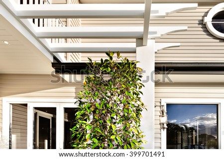 White wooden pillars and green ornamental plant beside a house front with dark windows and wooden bars - stock photo